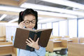 Schoolgirl reads textbook in classroom Royalty Free Stock Photo
