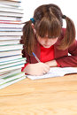 Schoolgirl schoolwork and stack of books makes written exercises in school notebooks Royalty Free Stock Images