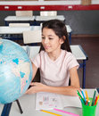 Schoolgirl searching places on globe at desk cute little in classroom Royalty Free Stock Images