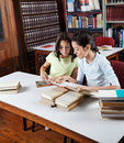 Schoolgirl showing book to classmate in library little while studying at table Royalty Free Stock Photo