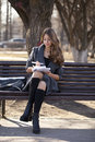 Schoolgirl sitting on a bench with a notebook in the spring park Royalty Free Stock Photo