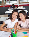 Schoolgirl sitting with classmate at desk in portrait of little classroom Stock Photo