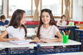Schoolgirl sitting with classmate looking at her portrait of cute desk while in classroom Royalty Free Stock Photography