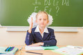 Schoolgirl sitting at desk, school classroom, on background of board Royalty Free Stock Photo