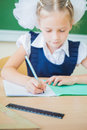 Schoolgirl sitting at desk at school and writing to notebook desktop background of a holding a pen ready in a for classwork on Stock Image