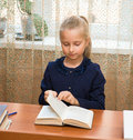 Schoolgirl studying and reading book at school little Stock Image