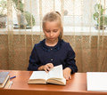 Schoolgirl studying and reading book at school little Stock Photography