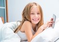Schoolgirl with tablet in bed at pretty lies home Royalty Free Stock Photos