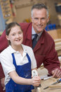 Schoolgirl and teacher in woodwork class Stock Photo