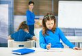 Schoolgirl thinking filling out test class teacher standing background Royalty Free Stock Images