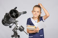 Schoolgirl wondered and looked up to by reading a textbook while standing at the telescope Royalty Free Stock Photo