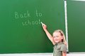 Schoolgirl writing on a blackboard Royalty Free Stock Photography