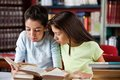 Schoolgirls reading book together in library while sitting at table Royalty Free Stock Photo