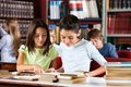 Schoolgirls reading book together at table in little while sitting library with classmates background Royalty Free Stock Photo