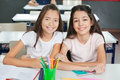 Schoolgirls sitting at desk in classroom portrait of young together Stock Photo