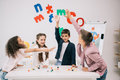 Schoolkids giving high five while studying with molecular model in classroom Royalty Free Stock Photo