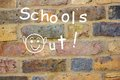 Schools out chalk graffiti on brick wall with happy face proclaiming school s Royalty Free Stock Photography