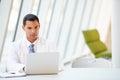 Schreibtisch Doktor-Using Laptop Sitting At im modernen Krankenhaus Stockfoto