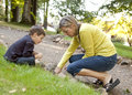 Science teacher and young boy looking for worms Stock Photo