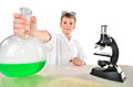 Scientist boy holds in his hand a big flask with green foaming liquid incide Royalty Free Stock Photo