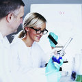 Scientist in chemical lab two conducting experiments Royalty Free Stock Photo