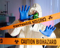 Scientist hazardous biochemicals laboratory behind caution tape in Royalty Free Stock Photography