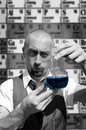 stock image of  Scientist holding flask with blue liquid on the periodic table of elements background