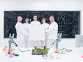 Scientist team in laboratory general view of five confident people a chemistry lab holding hands an empty banner around lab tools Royalty Free Stock Photography