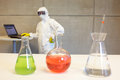 Scientist working in laboratory with chemicals white protective coveralls mask and goggles Stock Photography