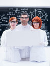 Scientists in chemistry lab close up of two beautiful girls students and a teacher a smiling and holding hands an empty banner and Stock Image