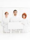 Scientists in chemstry lab close up of two beautiful women and a men a chemistry smiling the camera with a whiteboard with Royalty Free Stock Images