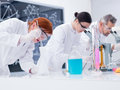 Scientists conducting lab experiments close up of three people in a chemistry chemical on a table with tools and colorful liquids Stock Image