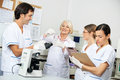Scientists discussing over blood sample in team of medical laboratory Royalty Free Stock Photos
