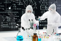 Scientists manipulating lab tools general view of two people studying and testing substances in a with and colorful liquids and a Royalty Free Stock Photo