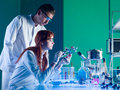 Scientists studying a molecular structure side view of two young caucasian in laboratory Stock Photography