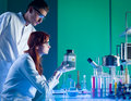 Scientists with toxic waste container close up of two caucasian looking at a plastic in a chemistry laboratory Royalty Free Stock Images