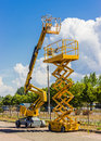 Scissor lift and articulated boom lift two types of mobile aerial work platform yellow hydraulic yellow hydraulic against the sky Royalty Free Stock Images