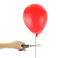 Scissors about to cut loose a balloon isolated on white Stock Image