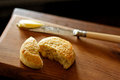 Scone or biscuit on wooden board with knife and butter Stock Photos