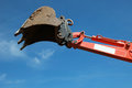 Scoop of an excavator raised over blue sky Stock Images