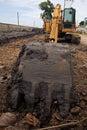 Scoop shovel of yellow excavator machine diging dirt Royalty Free Stock Images
