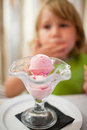 Scoops of strawberry ice cream in crystal cup and child behind Royalty Free Stock Photo