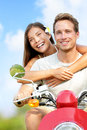 Scooter driving happy young couple fun in love multiracial having the free outdoor smiling caucasian men and asian woman Royalty Free Stock Photo