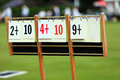 Scoreboard at a lawn bowls match with out of focus mat on grass and spectators in distance Stock Images