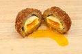 Scotch egg runny yolk cut in half on a wooden board Royalty Free Stock Photo