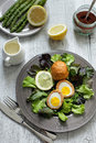 Scotch eggs with salad on a dark plate Royalty Free Stock Image