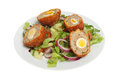 Scotch eggs and salad freshly made with on a plate isolated against white Royalty Free Stock Photo