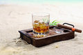 Scotch on the rocks beautiful image of in a classy wooden tray a sandy beach Royalty Free Stock Photo
