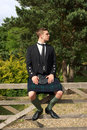 Scotsman in full dress kilt wear a young sitting on a gate Stock Photos