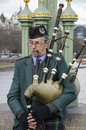 Scotsman playing the bagpipes in london england Stock Photos